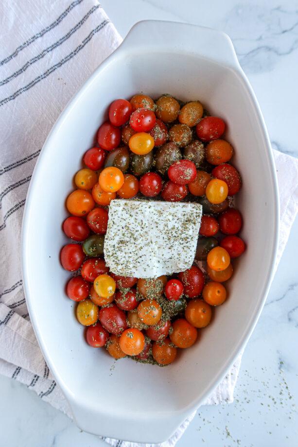 Tomatoes, feta & seasonings in a white baking dish, ready to bake!
